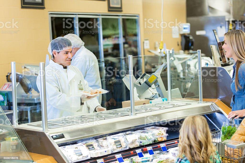 Deli employee packaging meat order for supermarket customer stock photo