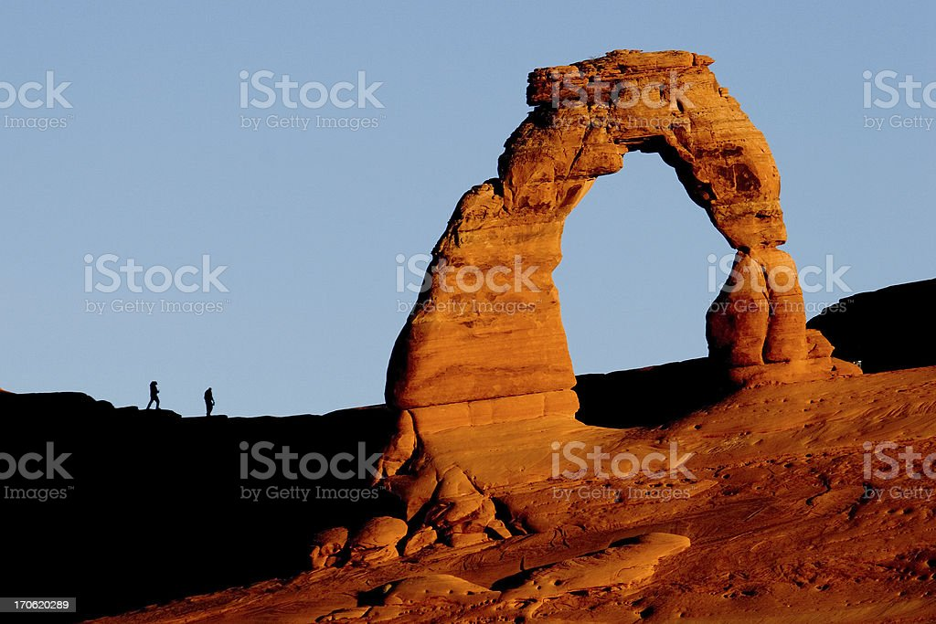 Delicate Arch & Hikers at Sunrise stock photo
