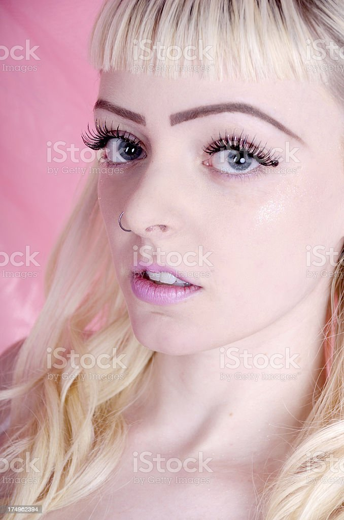 Delicate blonde with blue eyes on pink royalty-free stock photo