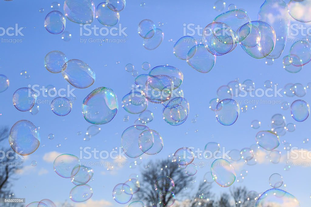 Delicate soap bubbles floating in blue sky stock photo