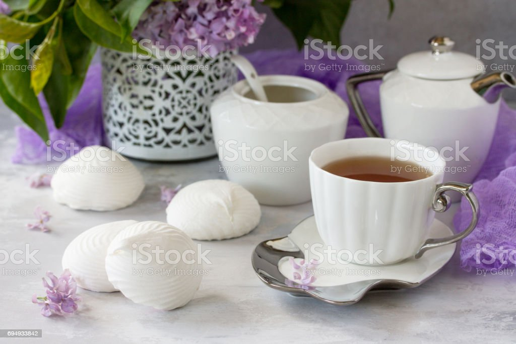 Delicate vanilla marshmallow on a white delicate plate. Still life with marshmallows, a cup of tea and lilac lilac on a background of ancient stone. stock photo