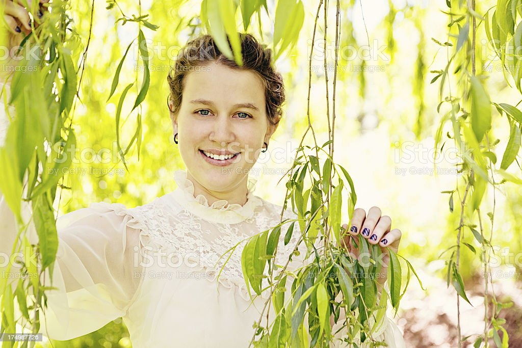 Delicately beautiful young woman in romantic gown smiles under tree royalty-free stock photo