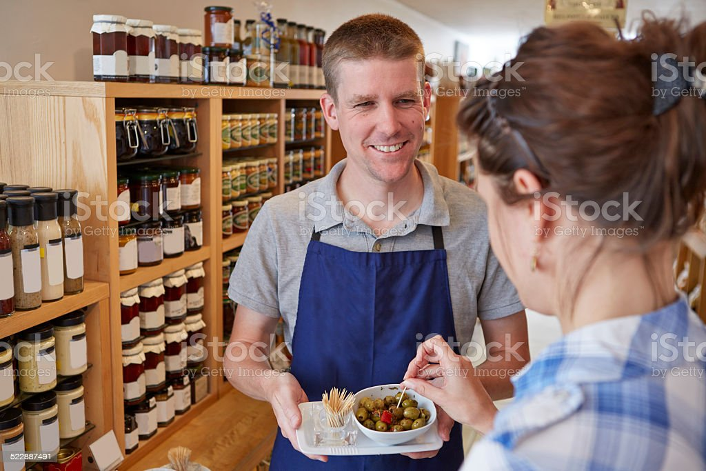 Delicatessen shop assistant offering customer olive stock photo