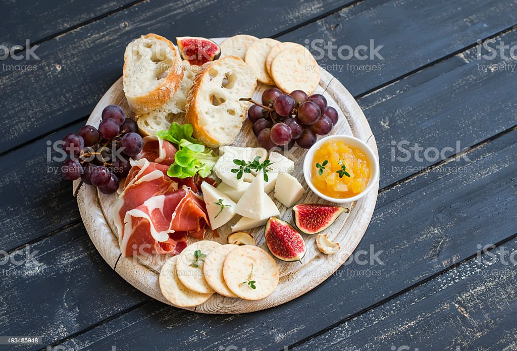 delicious appetizer to wine - ham, cheese, grapes, crackers, figs stock photo