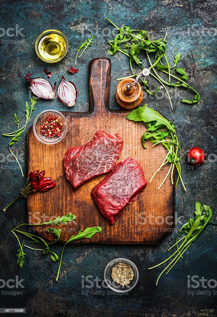 Delicious beef steak on vintage cutting board, top view stock photo