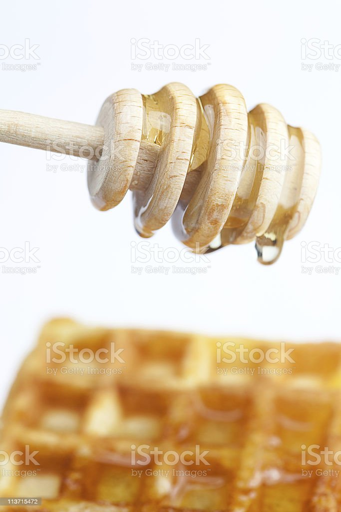delicious Belgian waffles and stick to honey isolated on white stock photo