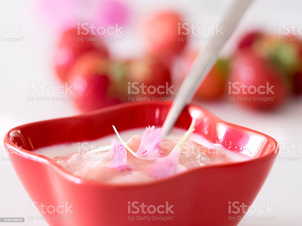 Delicious berry mousse with milk, strawberry and edible flowers royalty-free stock photo