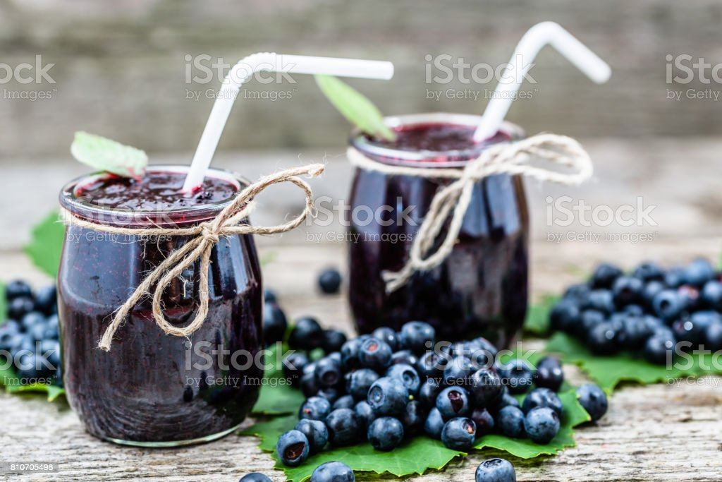 Delicious berry smoothie in jar and fresh blueberry fruits stock photo