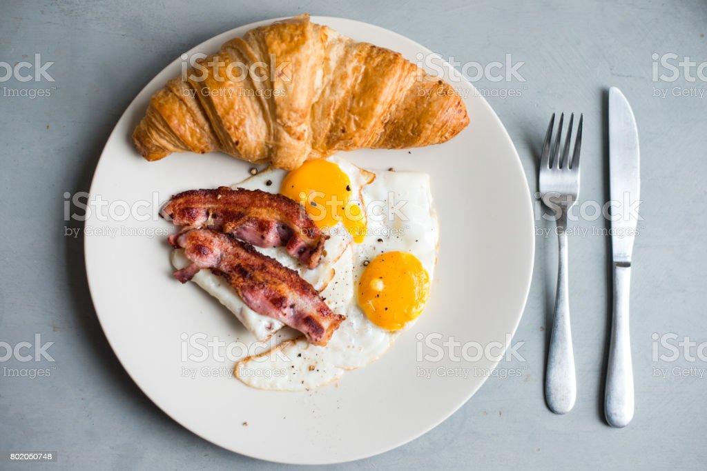 Delicious breakfast - eggs, bacon, croissant stock photo