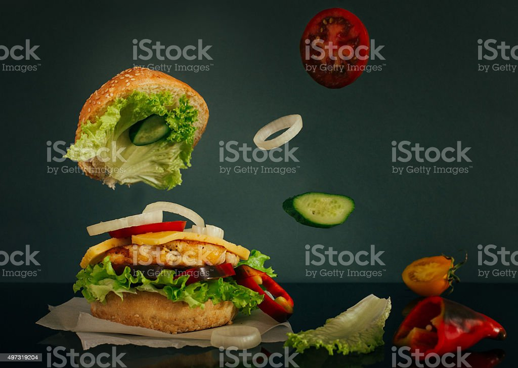 Delicious burger with flying ingredients on dark background stock photo