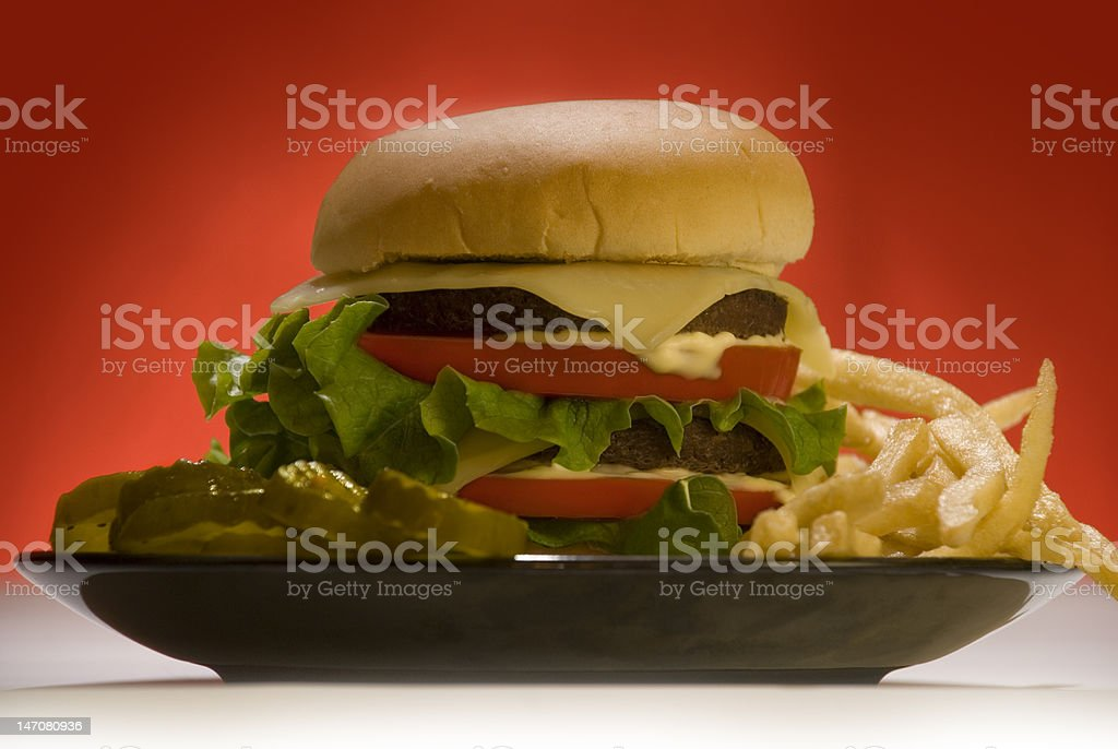 Delicious Burger with Fries and Pickles on Red Background royalty-free stock photo