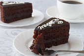 Delicious cake Sacher with coffee on a wooden background
