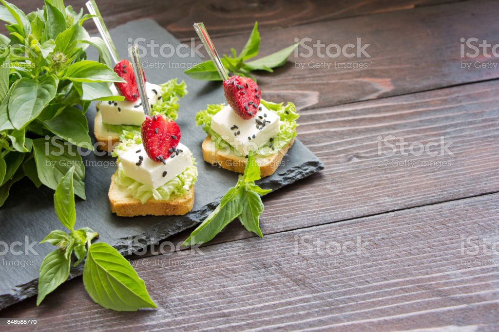 Delicious canapes wiyh feta cheese and strawberrys on background of fresh basil leaves.Banquet service stock photo