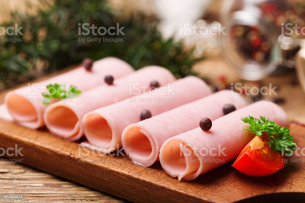 Delicious canned cooked ham on a wooden board with spices. stock photo