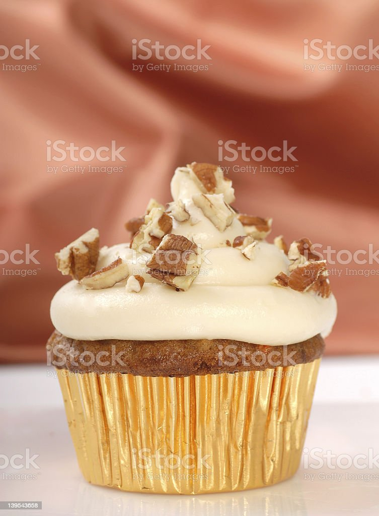 Delicious carrot cake cupcake with cream cheese frosting and nut royalty-free stock photo