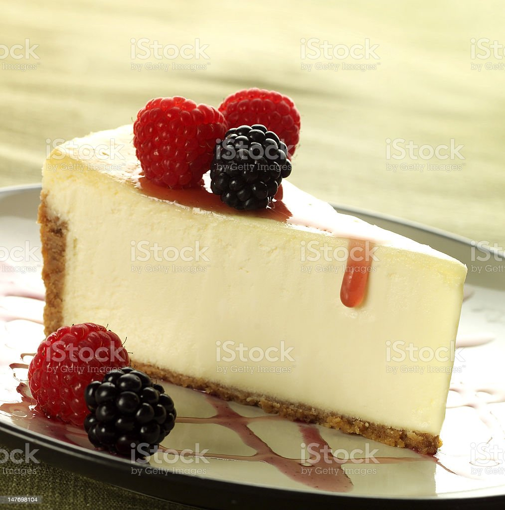 Delicious cheesecake slice with raspberries and blackberries royalty-free stock photo