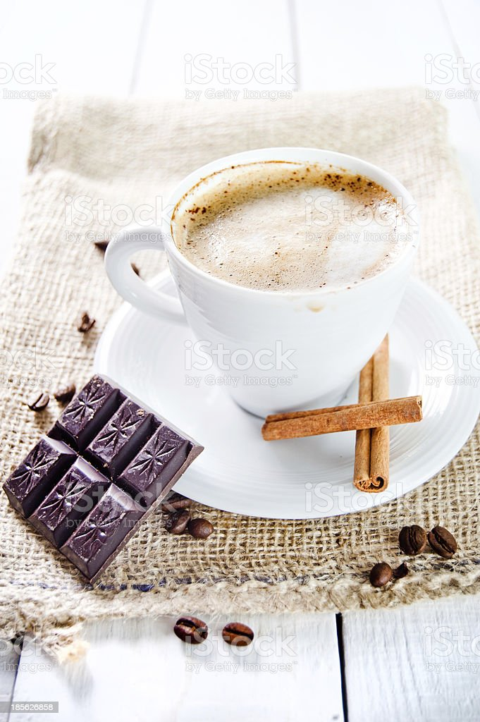 Delicious cup of cappuccino with cinnamon and chocolate royalty-free stock photo