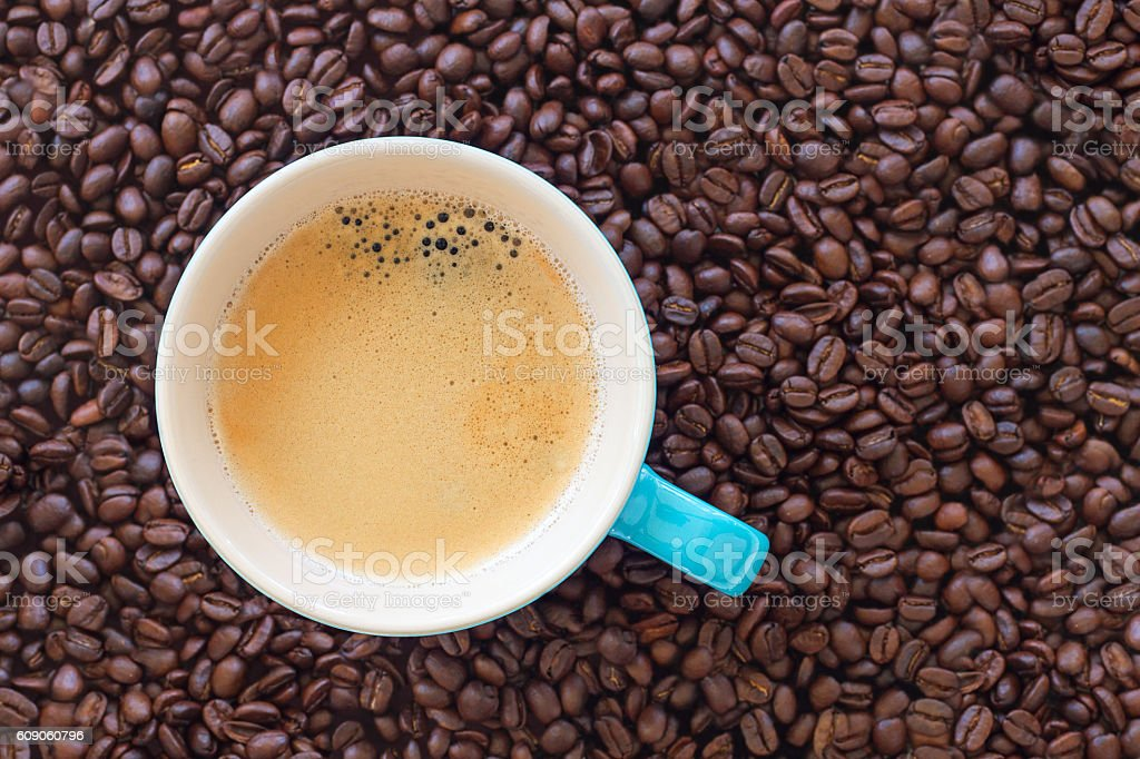 Delicious cup of coffee surrounded by roasted coffee beans stock photo