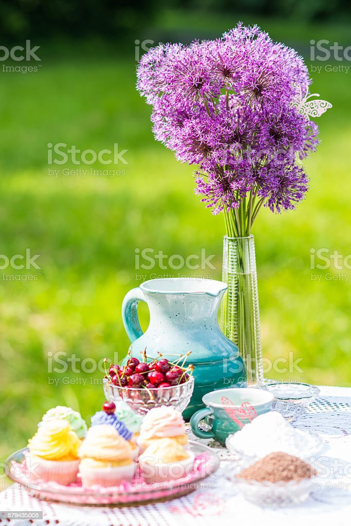 delicious cupcakes, cherry and jug on the table in the stock photo