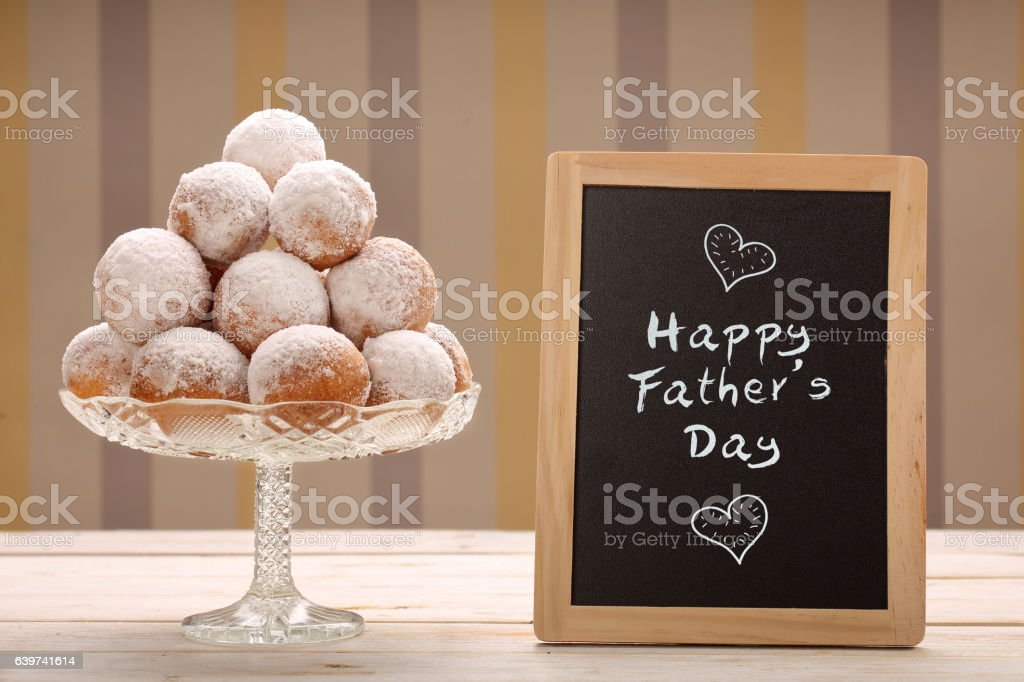 Delicious donuts and board with Happy Fathers Day inscription gr stock photo