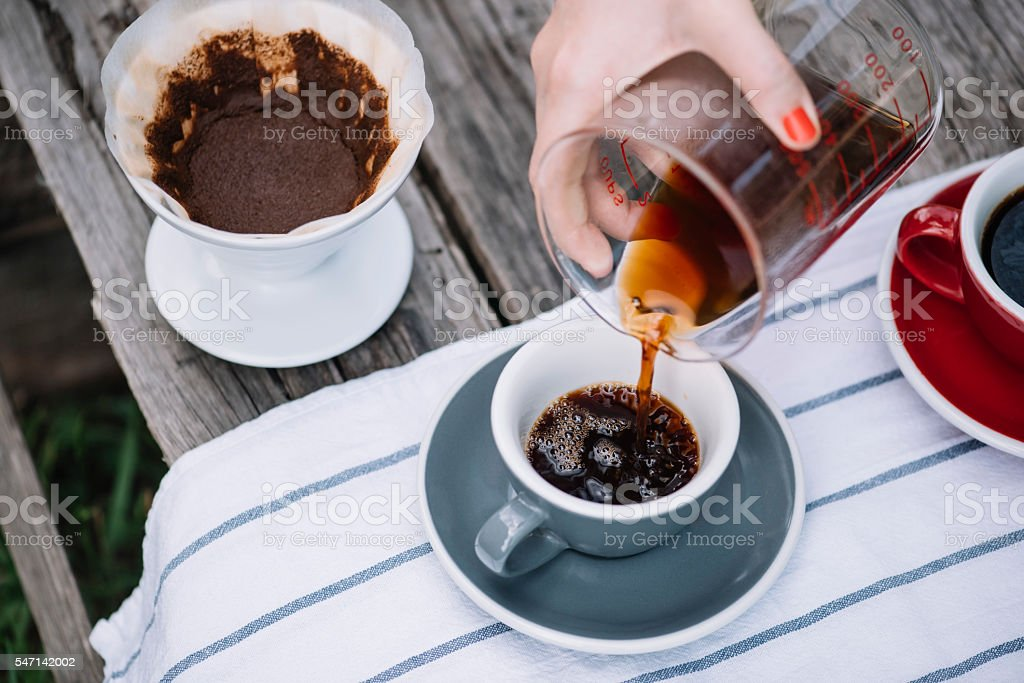 Delicious fresh pourover coffee pouring into the ceramic grey cup stock photo