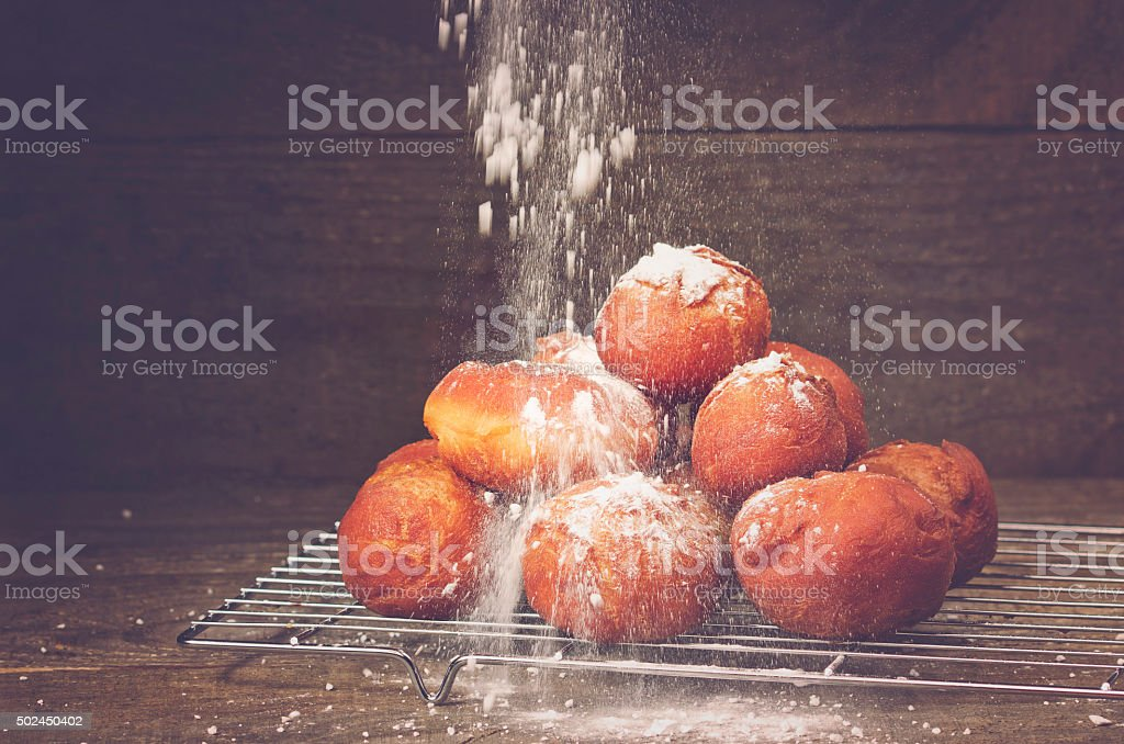 Delicious freshly baked donuts sprinkled with powdered sugar cooling stock photo