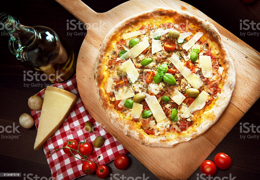 Delicious freshly baked pizza on a wooden paddle stock photo