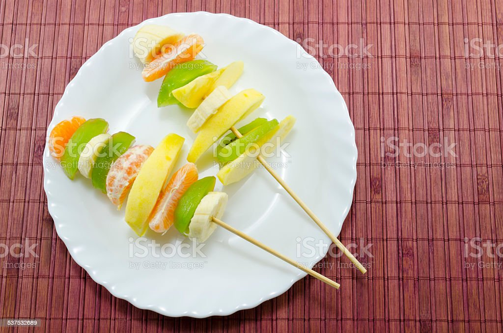 Delicious fruit skewers on a white plate royalty-free stock photo