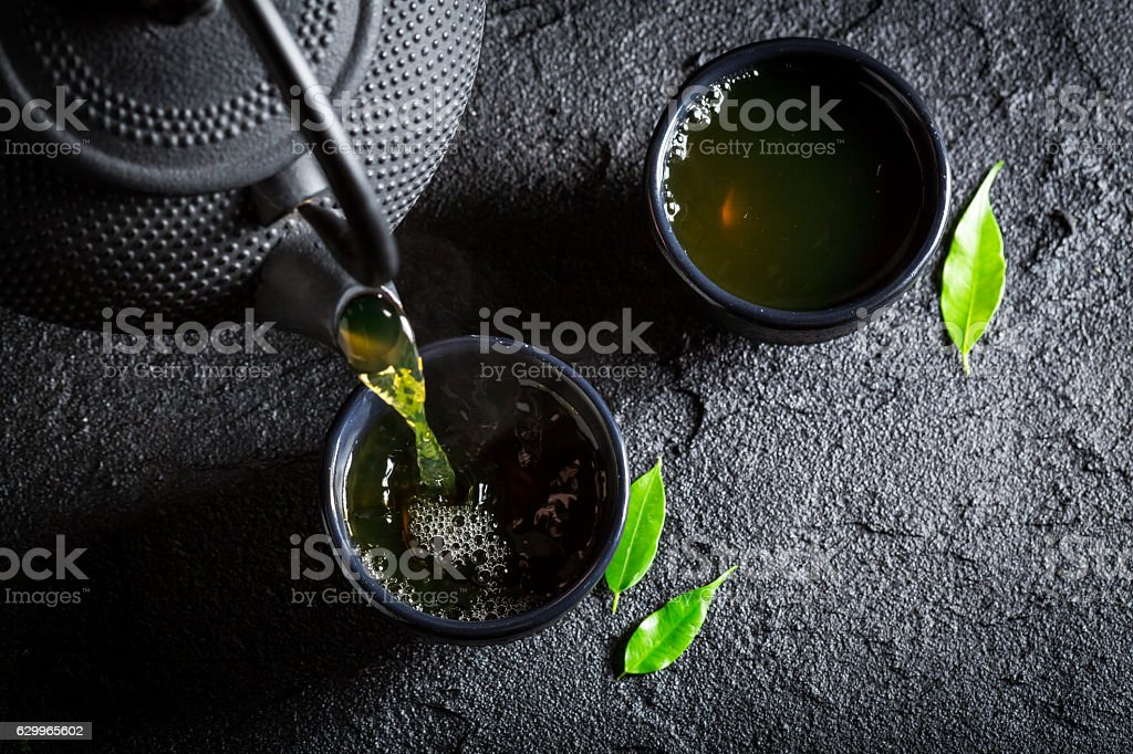 Delicious green tea with teapot and cup on black rock stock photo