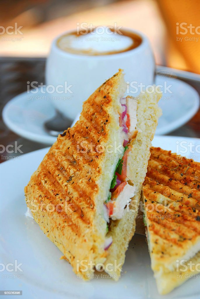 Delicious grilled sandwich on white plate with coffee behind stock photo