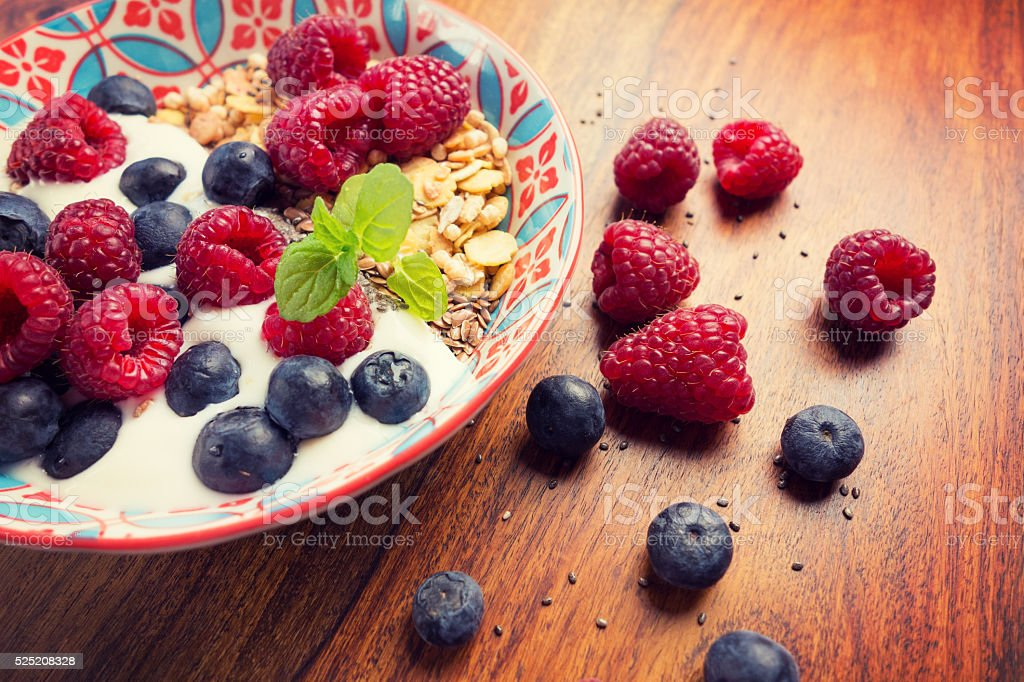 Delicious healthy breakfast with raspberries, blueberries, and a mint leaf stock photo