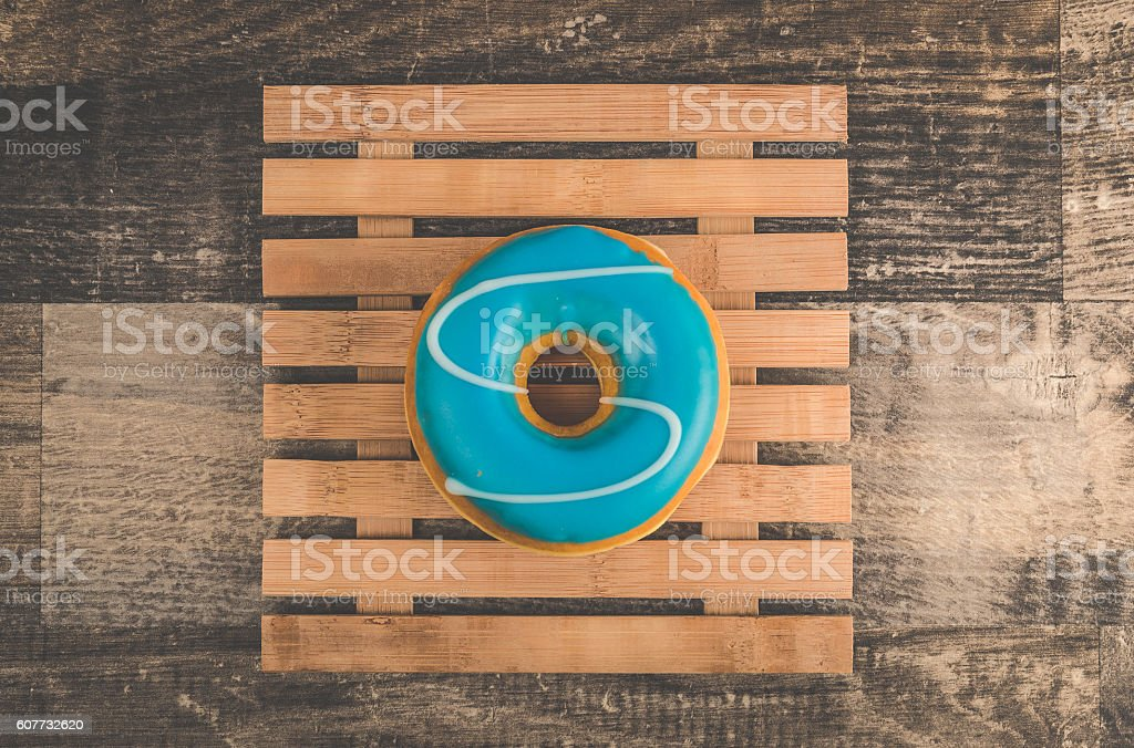 Delicious iced donut on a bamboo plate stock photo