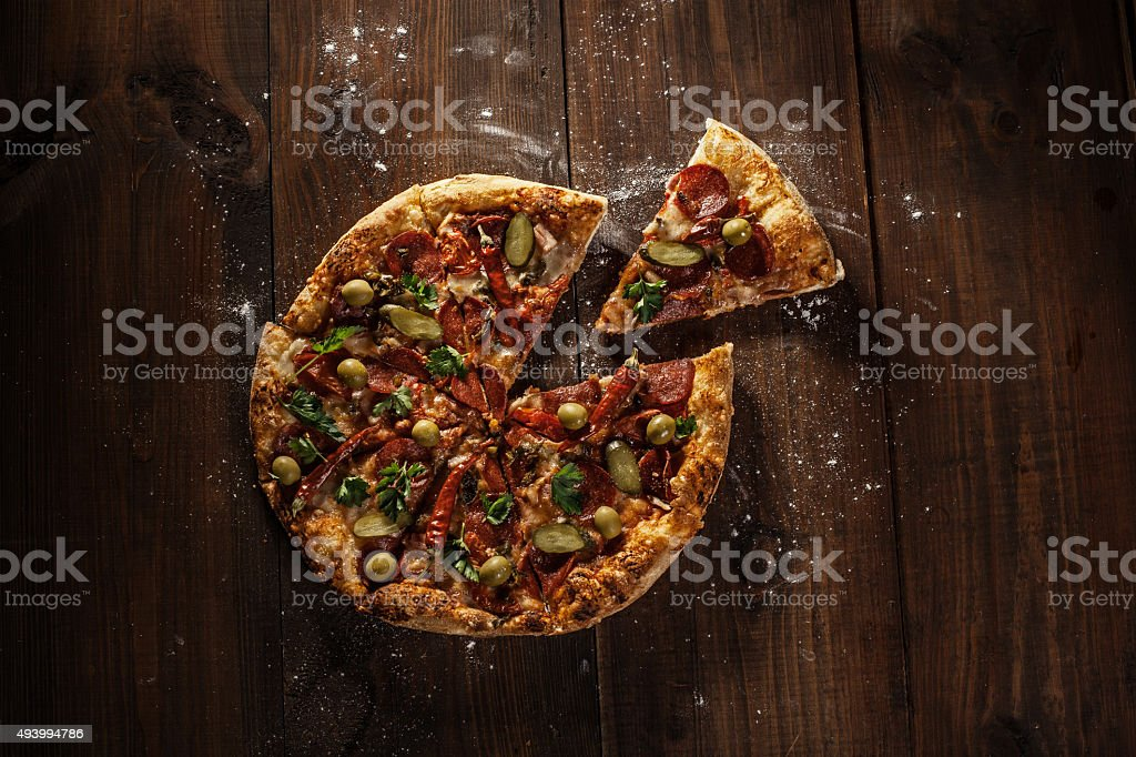 delicious italian pizza with slice served on wooden table stock photo