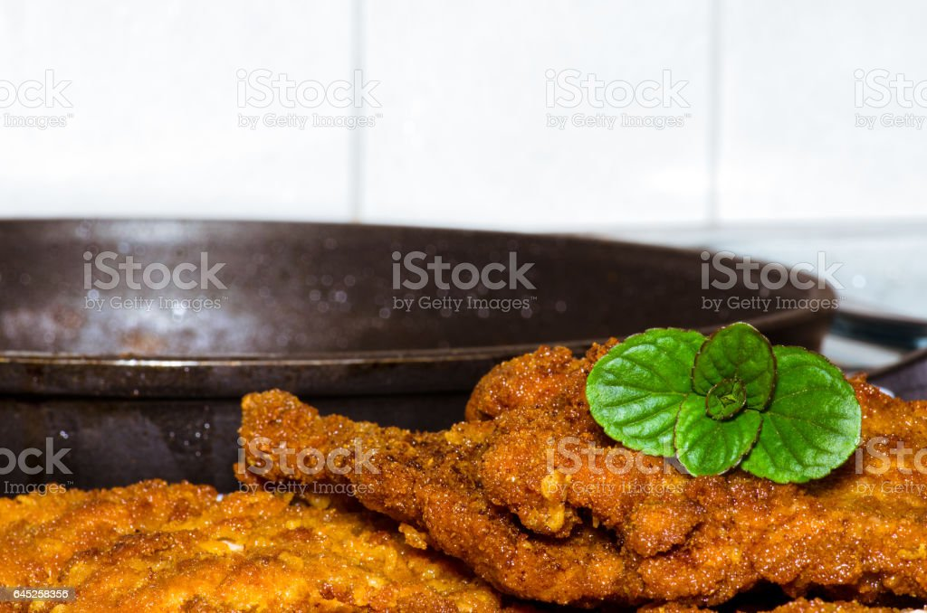 Delicious just cooked schnitzel with mint leaves for decor and frying pan in the background. stock photo