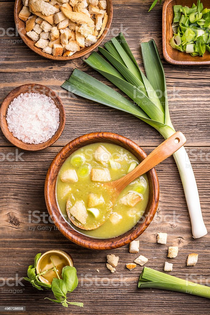 Delicious leek soup in wooden bowl stock photo