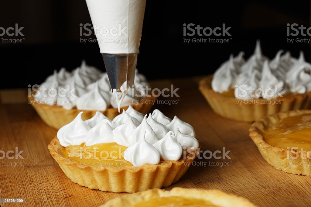 Delicious lemon curd tartlets  with meringue on wooden  table stock photo