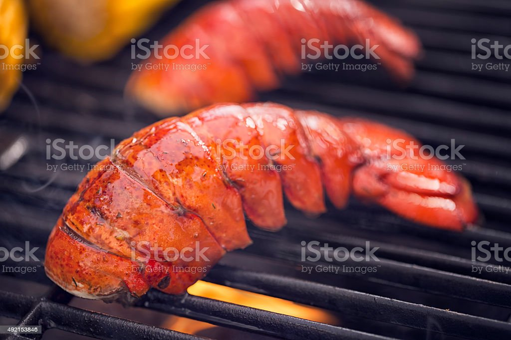 Delicious Lobster Tails and Sweetcorn on BBQ Grill stock photo