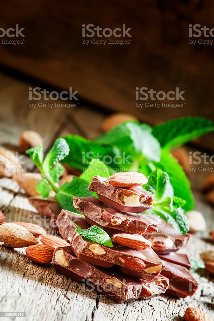 Delicious milk chocolate with whole almonds and mint leaves stock photo