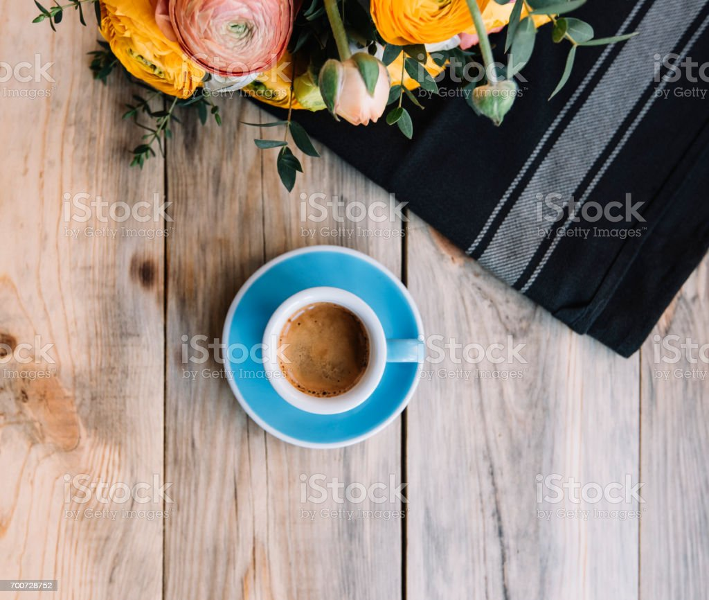 Delicious morning fresh cup of espresso coffee with a beautiful tiger crema in a blue cup, Ranunculus and eucalyptus flower bouquet, black cloth on the rustic wooden table background, flat lay stock photo