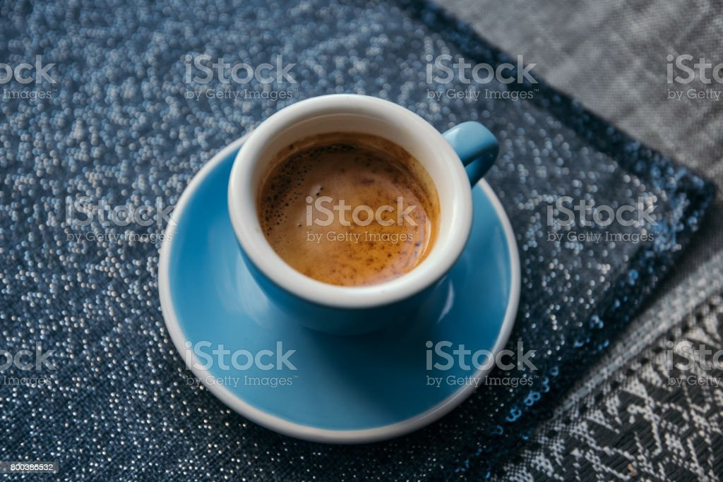 Delicious morning freshly brewed espresso coffee with a beautiful tiger crema. Photo is made in blue colors: blue mug, blue saucer, blue table napkin stock photo