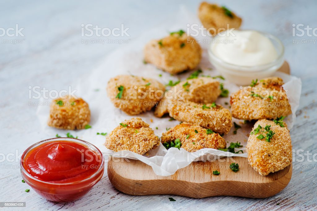 Delicious nuggets served on the board with two sauces stock photo
