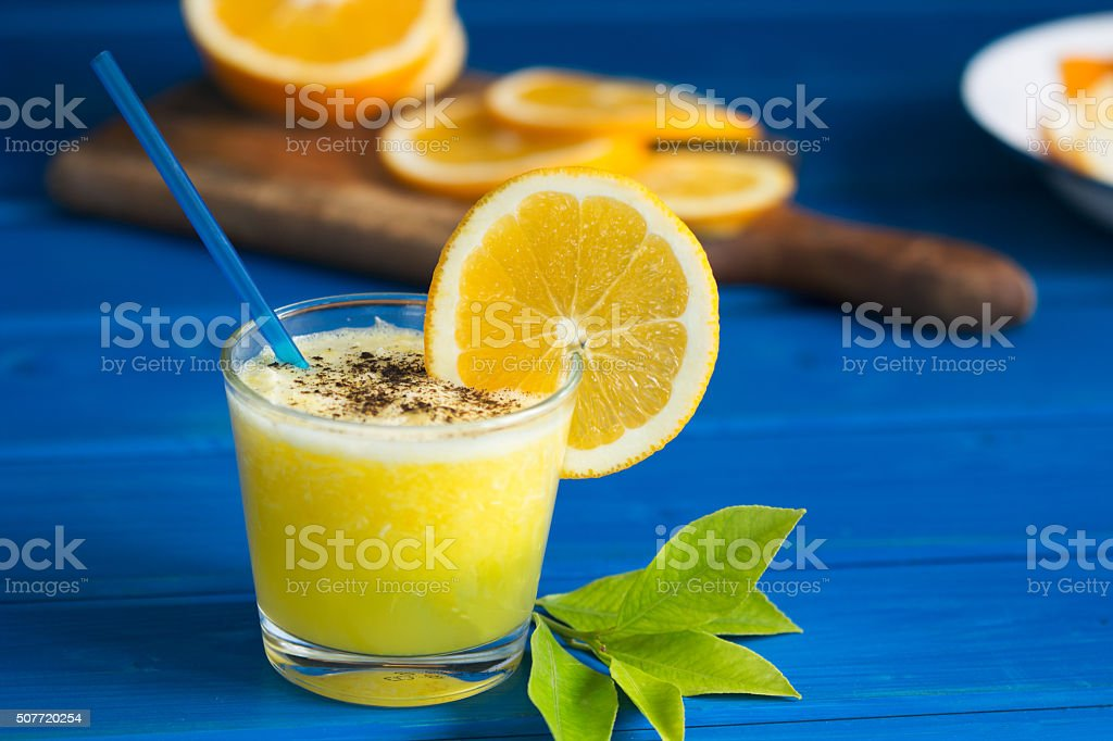 Delicious orange juice in glass  on  blue  wooden background royalty-free stock photo