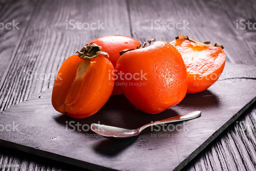 Delicious orange persimmons on wooden table ,healthy food. stock photo