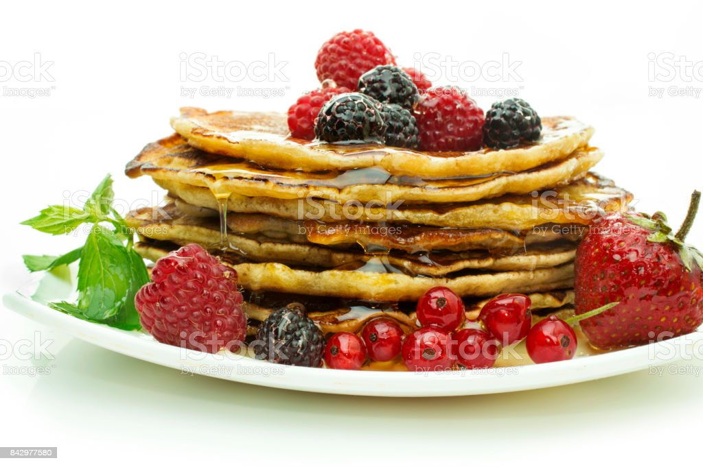 Delicious pancakes with berries and maple syrup on a white background stock photo