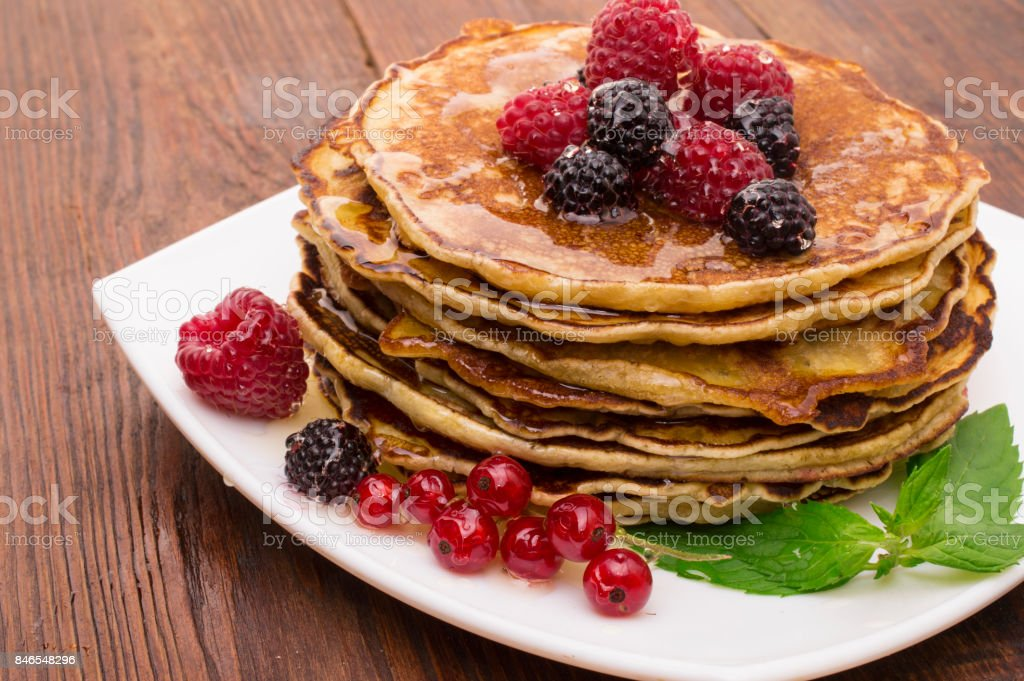 Delicious pancakes with berries and maple syrup stock photo