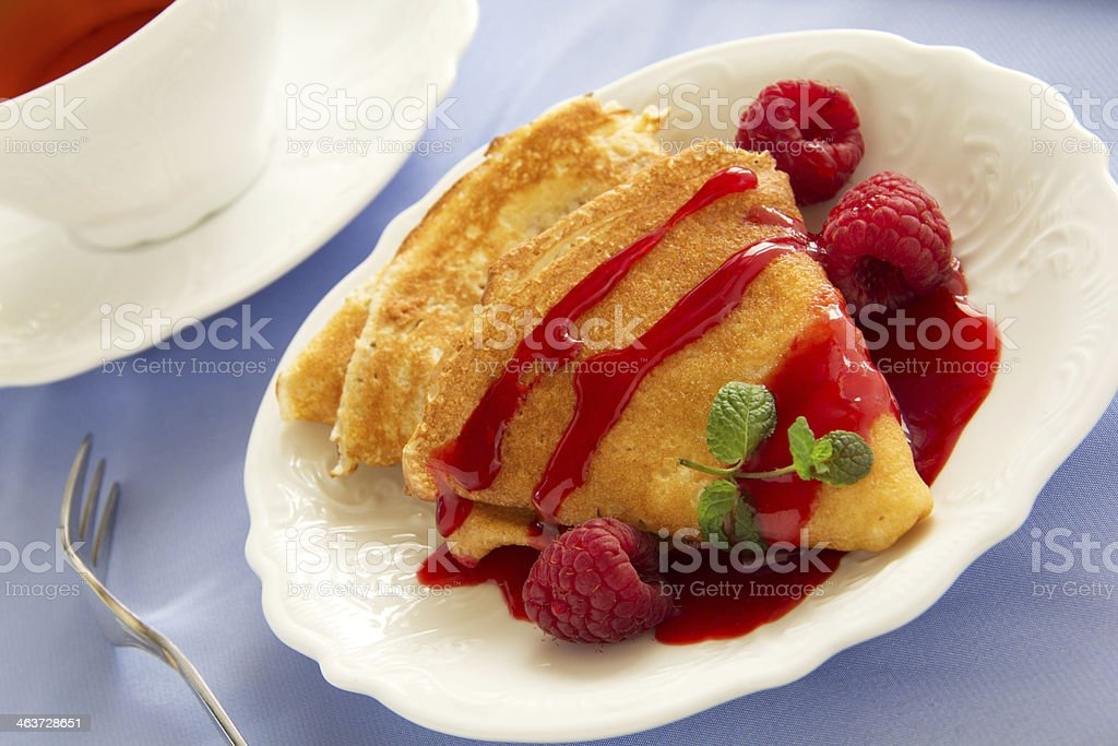 Delicious pancakes with berries  and raspberry sauce. stock photo