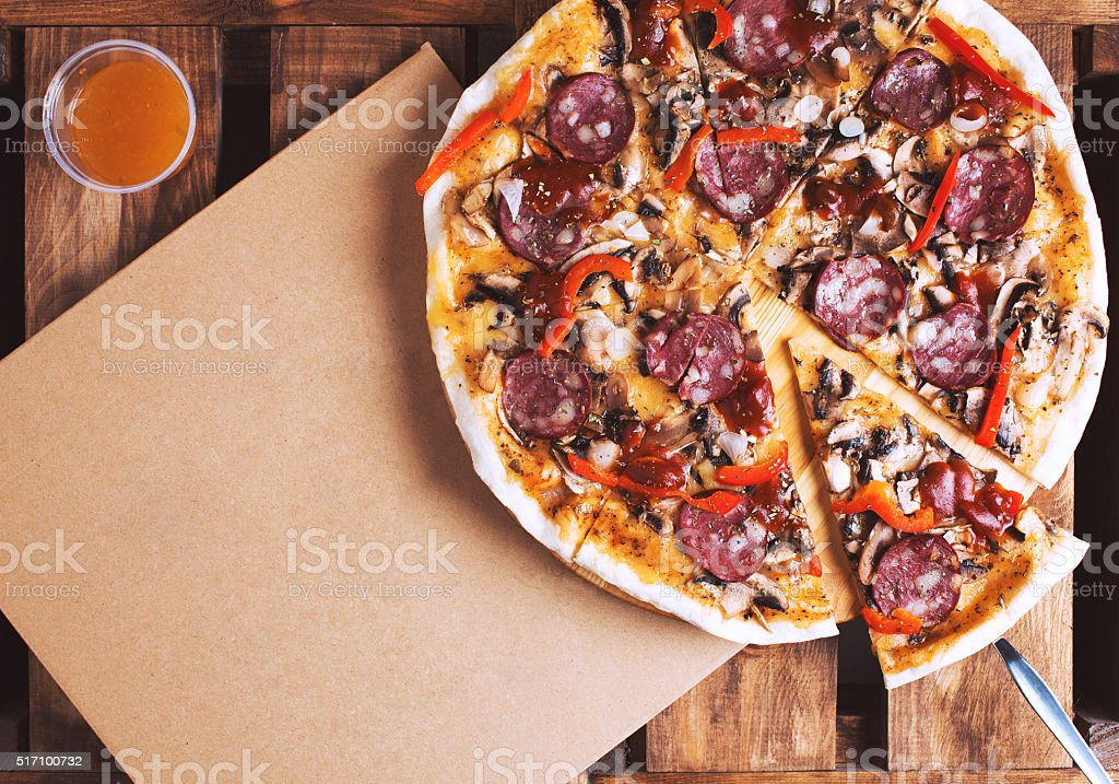 Delicious pizza and cardboard delivery box flat lay stock photo