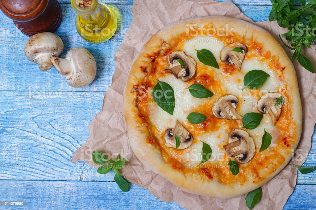Delicious pizza with mushrooms and basil stock photo