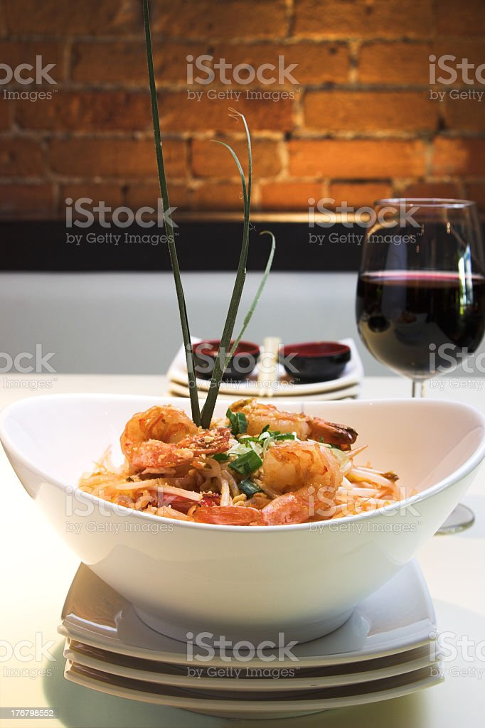 A delicious platter of shrimp pad thai with red wine stock photo
