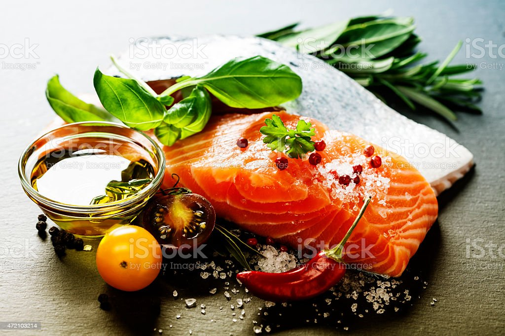 Delicious portion of fresh salmon fillet covered with herbs stock photo